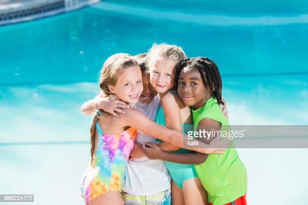 Multi-ethnic children in group hug by swimming pool
