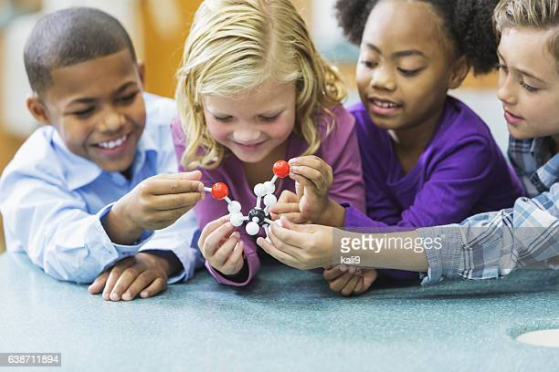 Multi-ethnic children in science class with model