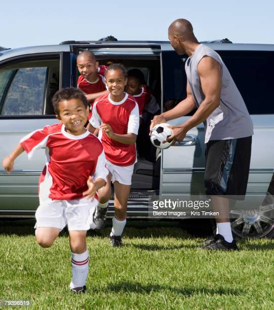 multi-ethnic children in soccer uniforms - practicing stock pictures, royalty-free photos & images