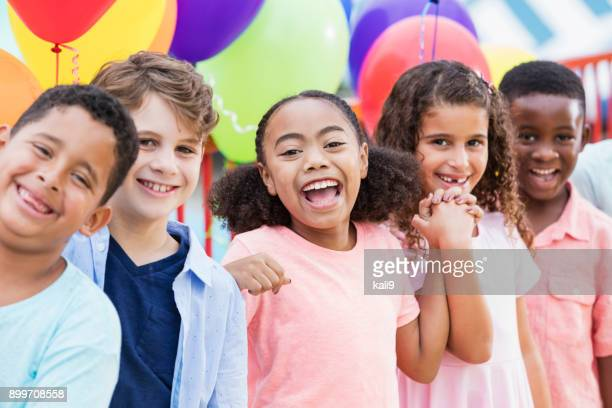 multi-ethnic children laughing, colorful balloons - birthday balloons stock photos and pictures