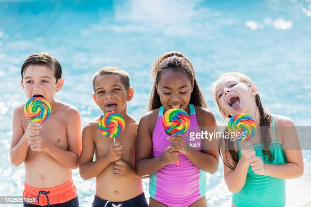 Multi-ethnic children licking lollipops by swimming pool