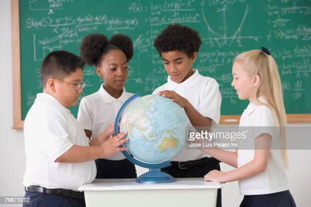 Multi-ethnic children looking at classroom globe
