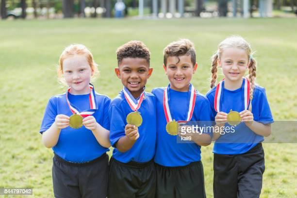 Multi-ethnic children on winning team, with medals
