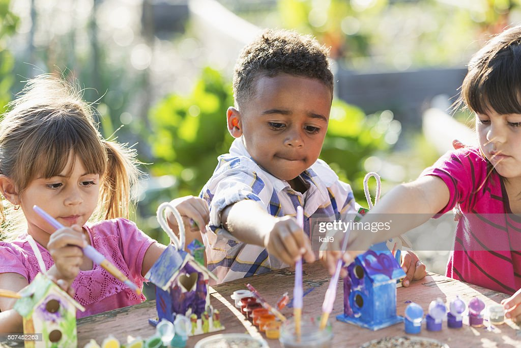 Multi-ethnic children painting bird houses outdoors : Stock Photo