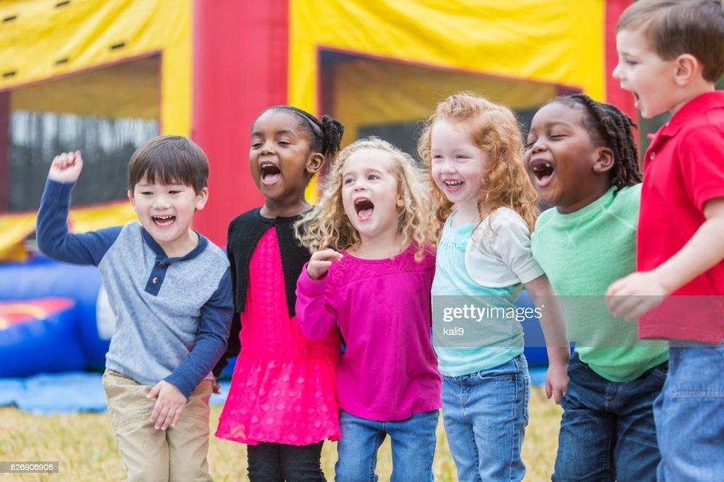 Y multiétnicos niños gritando, junto a la casa de la despedida : Foto de stock