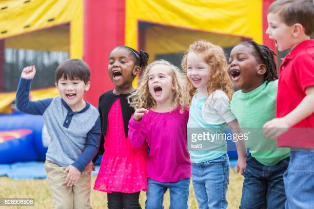 multi-ethnic children shouting, next to bounce house - gala stock pictures, royalty-free photos & images