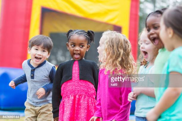 multi-ethnic children shouting, next to bounce house - fete stock photos and pictures