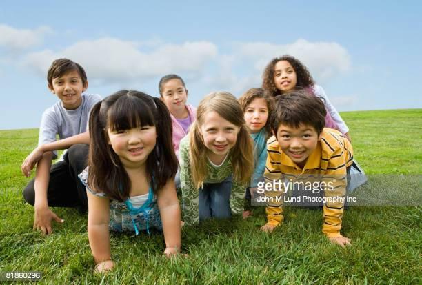 Multi-ethnic children sitting in grass