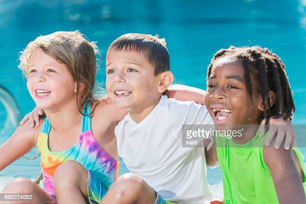 Multi-ethnic children sitting together by swimming pool