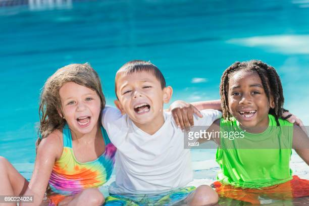 Multi-ethnic children sitting together in swimming pool