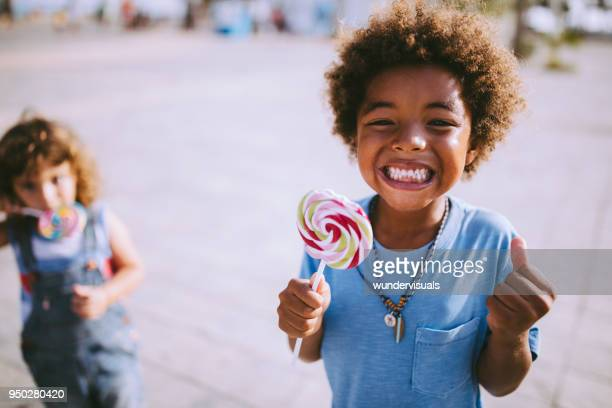 multi-ethnic children with colorful lollipops outdoors on summer vacations - lollipop stock pictures, royalty-free photos & images