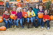 Multi-ethnic children with pumpkins at fall festival