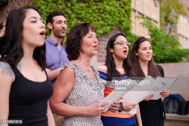 multi-ethnic choir singers performing outside language school - choir stock pictures, royalty-free photos & images