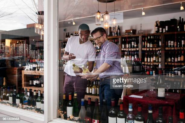 multi-ethnic colleagues discussing in wine shop - liquor store stock pictures, royalty-free photos & images