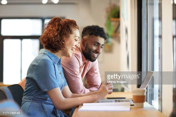 multi-ethnic colleagues discussing over laptop - smart casual stock pictures, royalty-free photos & images
