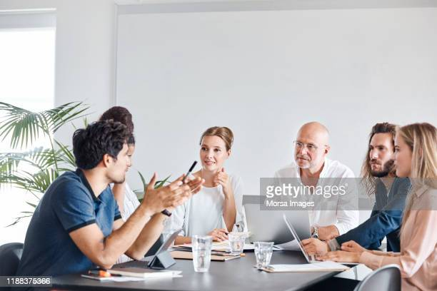 multi-etnische collega's plannen in meeting - teamwork stockfoto's en -beelden
