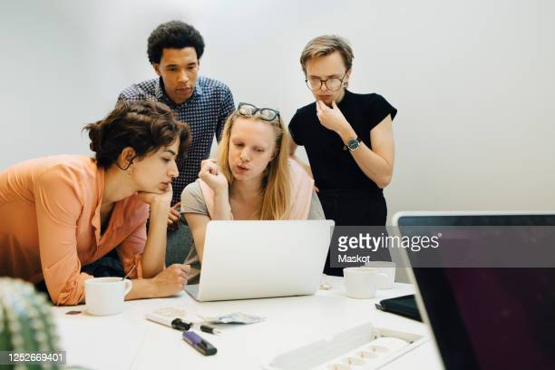 multi-ethnic colleagues planning strategy while looking at laptop in illuminated office board room - transgender stock pictures, royalty-free photos & images