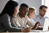 Multiethnic colleagues seated in coworking room discuss new corporate app