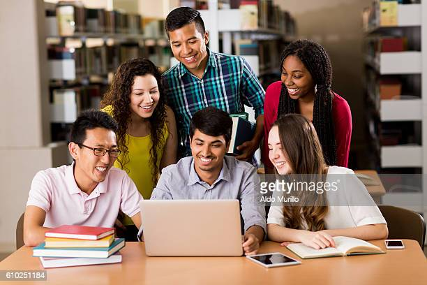 Multi-ethnic college students using laptop in the library
