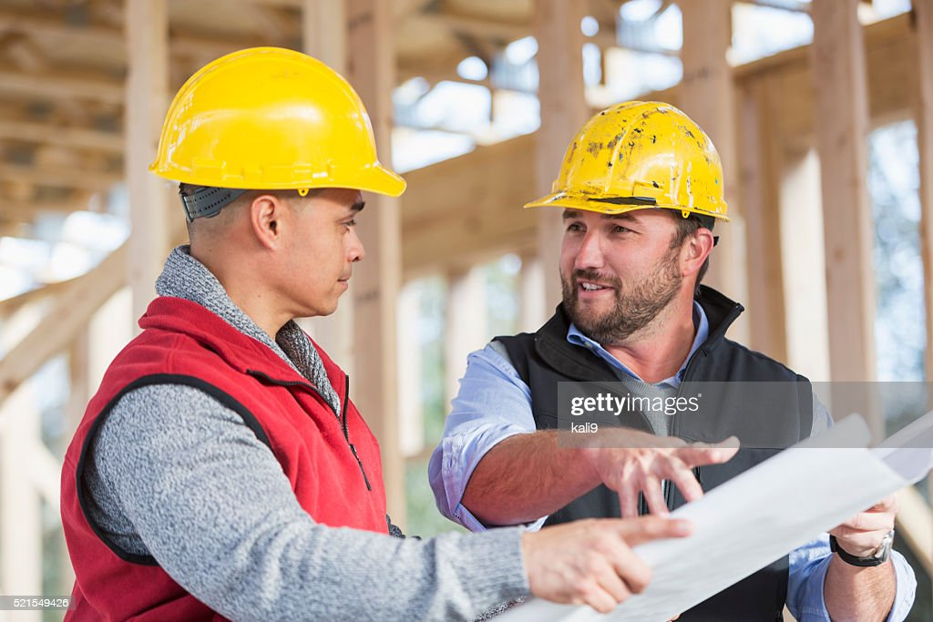 Multi-ethnic construction workers with plans, talking : Stock Photo