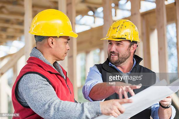 Multi-ethnic construction workers with plans, talking