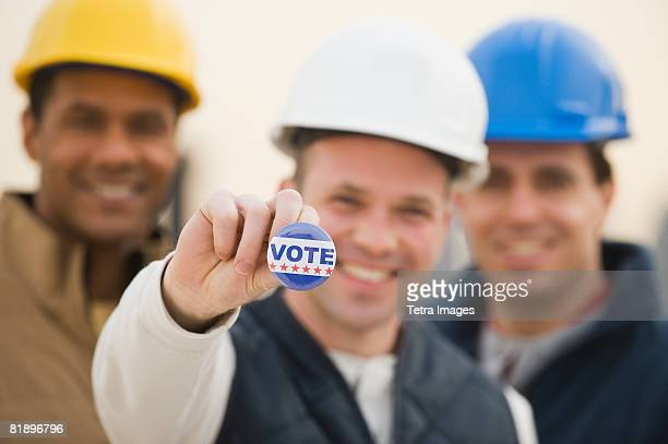 Multi-ethnic construction workers with Vote button