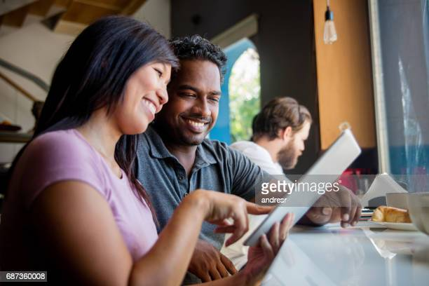 Multi-ethnic couple at a cafe using a tablet computer