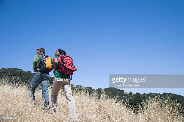 Multi-ethnic couple backpacking in rural area