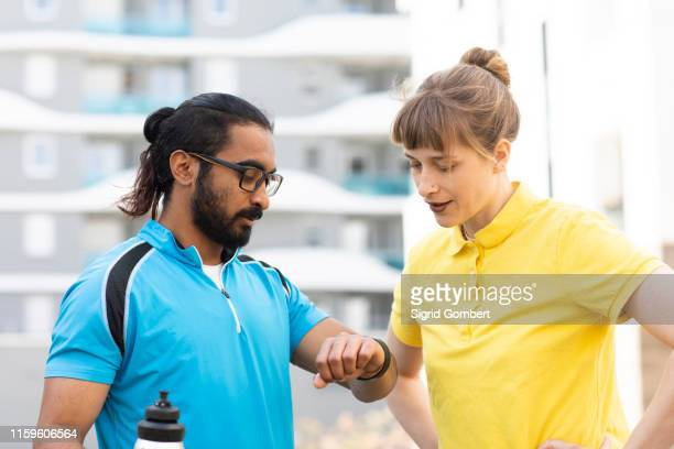 multi-ethnic couple checking time after exercise - sigrid gombert photos et images de collection