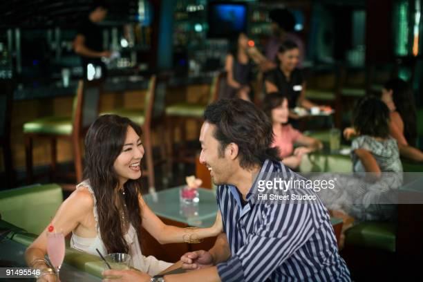 Multi-ethnic couple drinking cocktails in nightclub