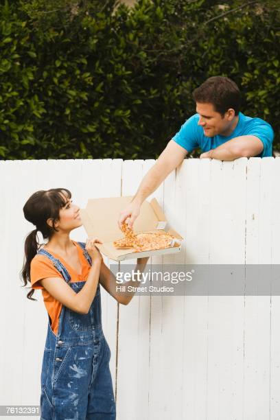 Multi-ethnic couple eating over newly painted fence