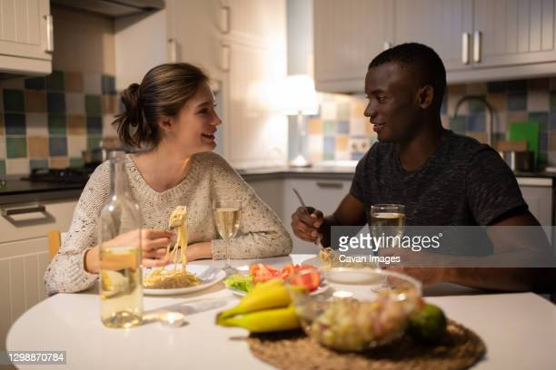 multiethnic couple enjoying pasta at home in evening - girlfriend stock pictures, royalty-free photos & images