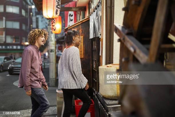 multi-ethniker-ehepaar in tokio restaurant in der nacht - eintreten stock-fotos und bilder