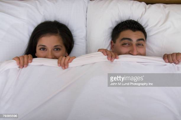 Multi-ethnic couple holding bed sheet over mouths