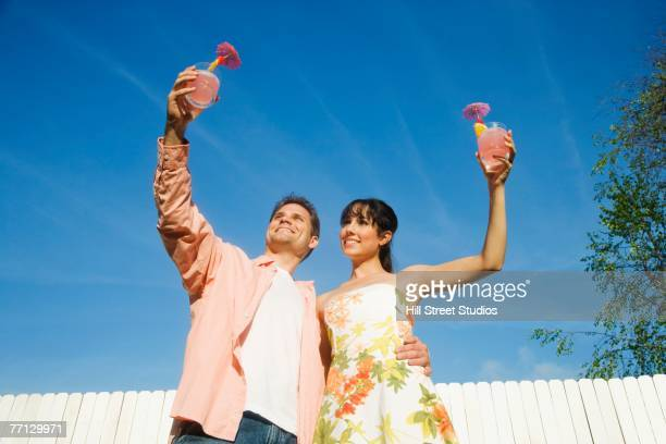 multi-ethnic couple holding cocktails - low angle view stock pictures, royalty-free photos & images