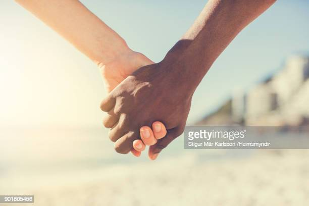 Multi-ethnic couple holding hands on sunny day