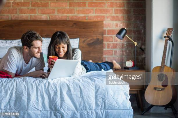 Multi-Ethnic Couple in Bed with Laptop