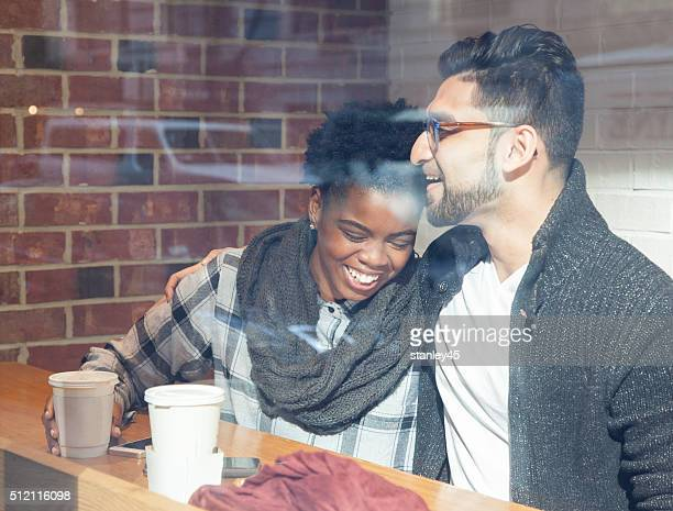 Multi-Ethnic Couple in Cafe with the city street window reflect