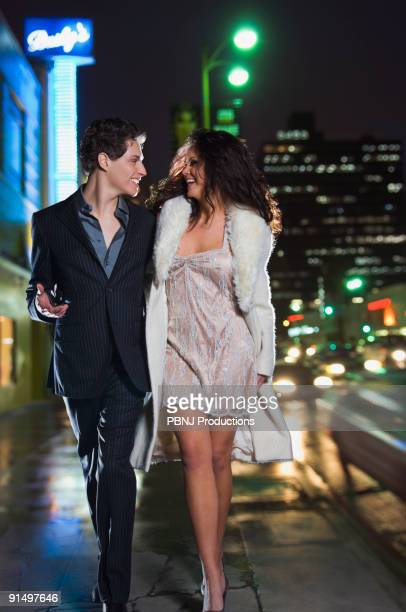 Multi-ethnic couple in formal attire walking down sidewalk