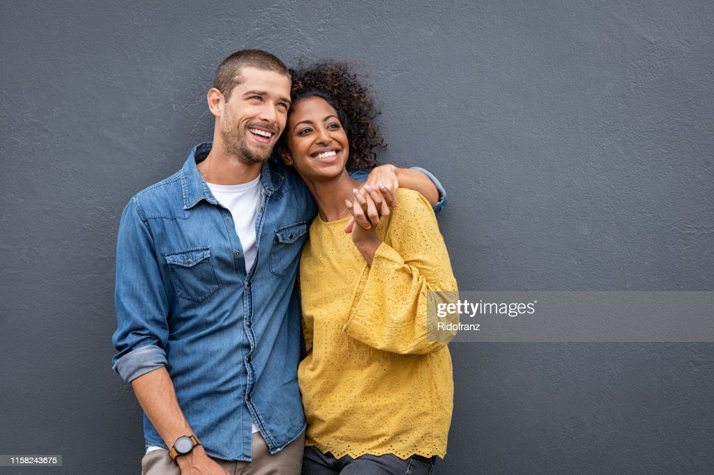 Multiethnic couple in love standing and holding hands : Stock Photo