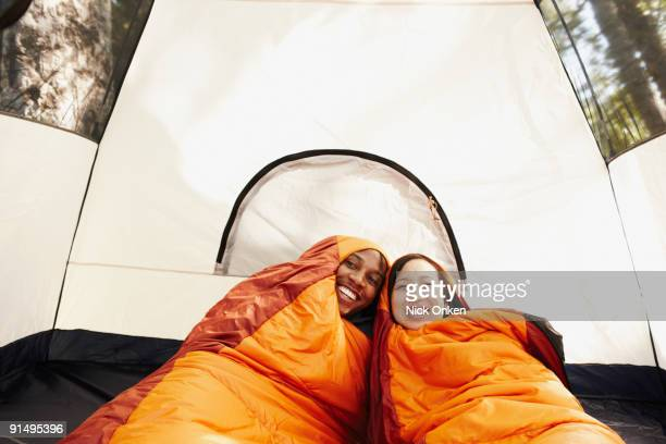 Multi-ethnic couple inside sleeping bags and tent