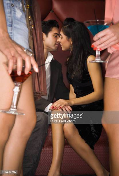 Multi-ethnic couple kissing at nightclub