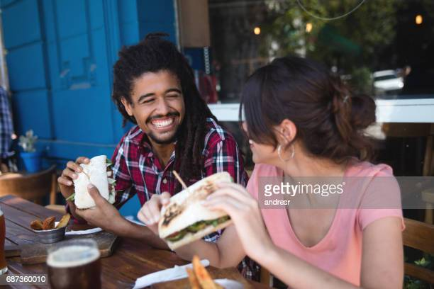 Multi-ethnic couple laughing while eating at a cafe