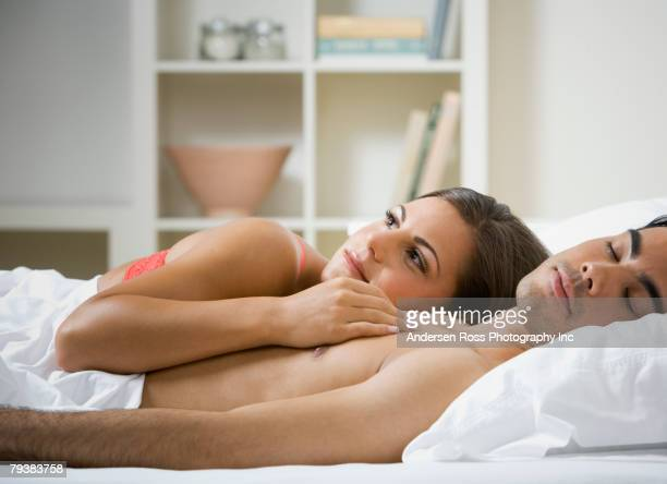 multi-ethnic couple laying in bed - romantic young couple sleeping in bed stock photos and pictures