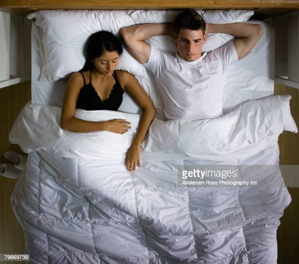 Multi-ethnic couple laying in bed