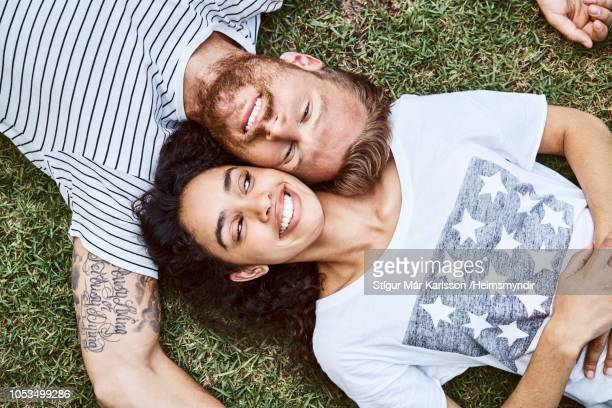 multi-ethnic couple lying on grass at back yard - lying down stock pictures, royalty-free photos & images