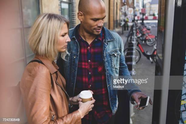 Multi-ethnic couple operating bike vending machine on sidewalk in city