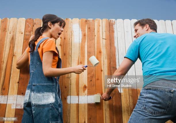 multi-ethnic couple painting fence - teasing stock pictures, royalty-free photos & images