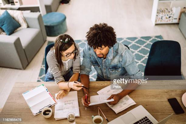 multi-ethnic couple planning their home budget - financial bill stock pictures, royalty-free photos & images