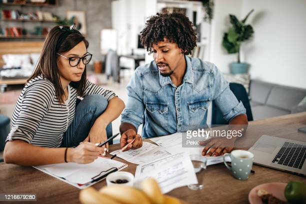 multi-ethnic couple planning their home budget - debt stock pictures, royalty-free photos & images